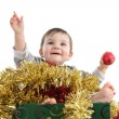 Pretty baby girl inside a box with christmas ornaments — Stockfoto