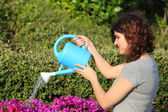 Beautiful woman watering flowers with a watering can — Stock Photo