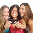 Group of three teenager girls laughing looking the smart phone — Stock Photo