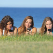 Group of three teenager girls typing on the mobile phone lying on the grass — Stock Photo #30323585