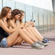Stock Photo: Group of three teenager girls typing on the mobile phone