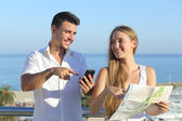 Couple discussing map or smartphone gps on vacations — Stock Photo