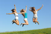 Group of three teenager girls jumping on the grass — Stock Photo
