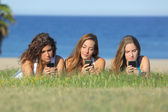 Group of three teenager girls typing on the mobile phone lying on the grass — Stock Photo