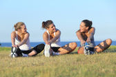 Group of three women stretching after sport — Stock Photo