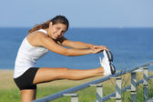 Beautiful woman stretching legs looking at camera — Stock Photo