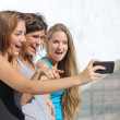 Group of three teenager girls amazed watching the smart phone — Stock Photo