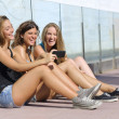 Stock Photo: Group of three teenager girls laughing while watching the smart phone