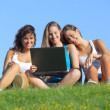 Group of three teenager girls laughing while watching the laptop outdoor — Stock Photo