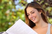 Beautiful teenager girl studying reading a notebook outdoor — Stock Photo