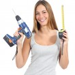 Beautiful woman holding a power drill and a tape measure — Stock Photo #32036045