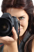 Close up of a photographer woman holding a digital slr camera — Stock Photo