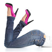 Beautiful woman legs with jeans and fuchsia high heels lying down — Stock Photo
