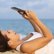 Side view of a teenager girl browsing her tablet pc lying on the sand of the beach — Stock Photo #35208015