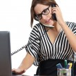 Beautiful secretary stressed at the phone working in the office — Stock Photo