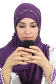 Arab woman writing a message addicted to the smart phone — Zdjęcie stockowe