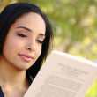 Close up of a beautiful woman reading a book in a park — Stock Photo #37983565