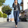 Fashion woman walking on the street talking on the mobile phone — Stock Photo