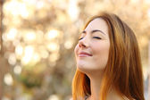 Beautiful woman doing breath exercises with an autumn background — Stock Photo