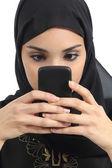 Vooraanzicht van een Arabische vrouw verslaafd aan de slimme telefoon — Stockfoto