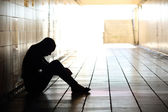 Teenager depressed sitting inside a dirty tunnel — Stock Photo