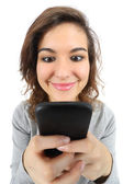 Wide angle view of a pretty teenager girl happy with a smart phone — Stock Photo