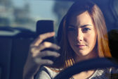 Front view of a woman driving a car and typing on a smart phone — Stock Photo