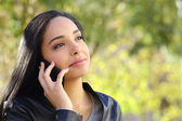 Arab business woman on the mobile phone in a park — Stock Photo