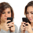 Two teenagers addicted to the smart phone technology — Stock Photo #39348921
