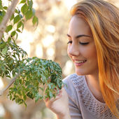 Beautiful woman taking care of a little tree — Stock Photo