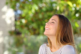 Young happy smiling woman doing deep breath exercises — Stock Photo