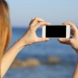 Back view of a woman taking photo with a smart phone camera — Stock Photo #42811039