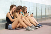 Group of teenager girls smiling happy texting on the smart phone — Stock Photo