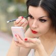 Beautiful woman making up eyelashes herself — Stock Photo #43708169
