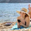 Pretty happy woman reading a smart phone on the beach — Stock Photo #45628633