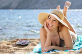 Happy woman thinking and looking at side lying on the beach — Foto de Stock
