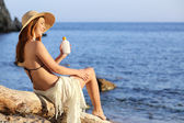 Woman on holidays  on the beach applying sunscreen protection on leg — Stock Photo