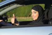 Happy arab saudi woman driving a car with thumb up — Stock Photo
