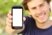 Uomo felice mostrando una schermata vuota cellulare all'aperto — Foto Stock