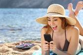 Sahilde bir akıllı telefon olarak sosyal medya izlerken kadın komik şaşırttı — Stok fotoğraf