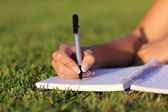 Close up of a woman hand writing on a notebook outdoor — Stock Photo