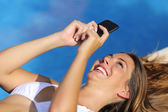 Funny woman using her smart phone in summer vacations — Stockfoto