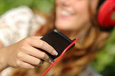 Woman hand using a smart phone to listen to the music with headphones — Stock Photo