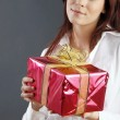 Beautiful young woman with a gift — Stock Photo