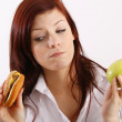 Young woman with hamburger and apple — Stock Photo