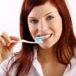Beautiful woman using a toothbrush and toothpaste — Stockfoto