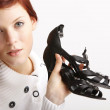 Young Woman Holding Shoes - Stock Photo