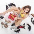 Girl sitting on the floor with shoes and a gift — Stock Photo #15778681