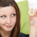 Girl with a condom near the sofa — Stock Photo #15779015