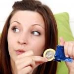 Girl with a condom near the sofa — Stock Photo #15779019